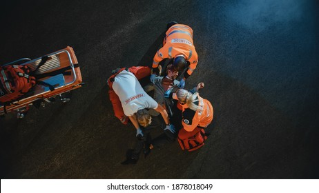 Aerial Portrait of a Young Injured Man Involved in Traffic Accident is Being Saved by Medical Team of EMS Paramedics on the Street at Night. Emergency Care Assistants Provide Essential First Aid Help.