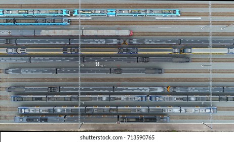 Aerial railway hub top down view showing passenger trains on tracks next to each other