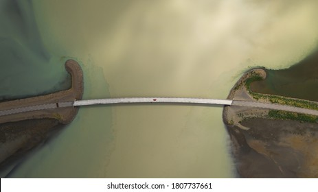Aerial Red car is driving over the bridge glacial white milky river in Iceland