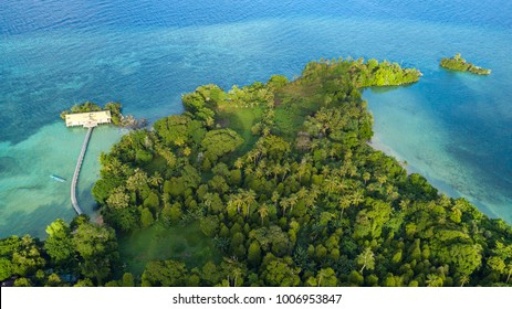 Aerial resort and wild tropical forest and coastline view over Hatta island, Maluku, Indonesia