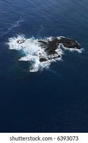 Aerial of rock in Pacific ocean off coast of Maui, Hawaii.