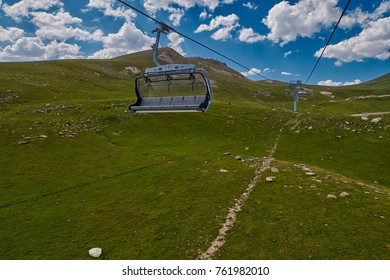 Aerial ropeway high in the mountains of Caucasus with grass plains and cow pastures in the background