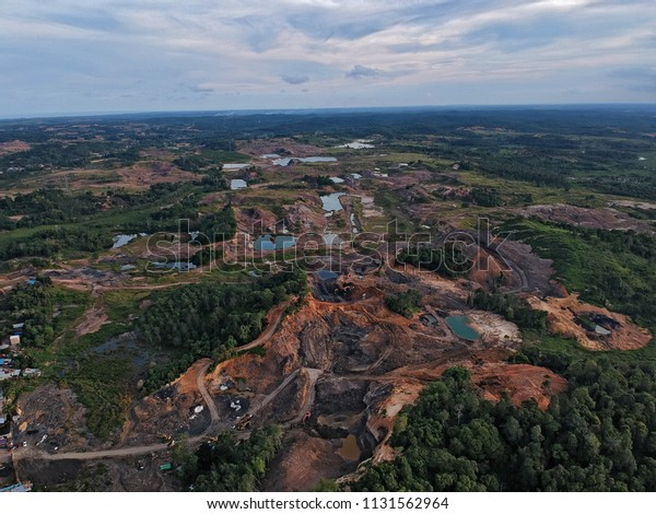 Aerial sad view of devastated country with many coal mines in East Kalimantan (Borneo) with the rest of the jungle in the back