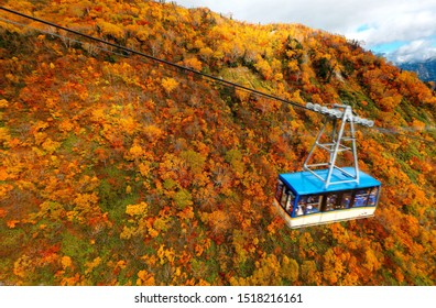 Aerial scene of a cable car flying over the gorge between Daikanbo & Kurobe Dam in Tateyama Kurobe Alpine Route, Toyama, Japan, with a breathtaking view of beautiful fall colors on the rugged mountain
