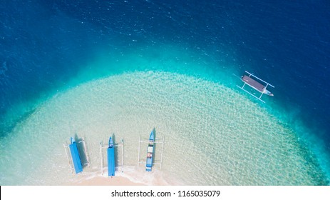 Aerial scenery of beautiful Gili Kedis island with turquoise water and traditional tourist boats in Lombok, Indonesia
