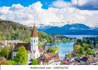 Aerial Scenery of Old Town Cityscape from Thun Castle and Alpine Mountain Range in Switzerland with Cloudy. Swiss Village among Swiss Alps. Scenic Landscape of Switzerland Country with Snowy Mountain.