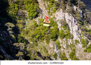 Aerial scenic view of cable car in Mount Ai-Petri, Crimea, Russia. The cabin mountain lift on the green mountain slope background. Scenery of Southern Crimea coast with a cable car in summer.