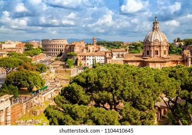 Aerial scenic view of Colosseum, Roman Forum in Rome and church of Santi Luca e Martina, Italy. Rome architecture and landmark.