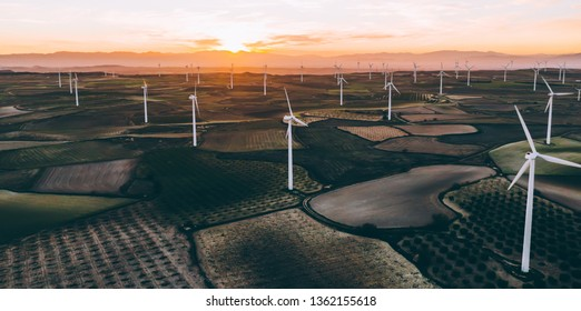 Aerial scenic view of renewable windmills turbines supplying cultivation area with eco power getting energy from wind blowing on vast area of agriculture meadows. Alternative electricity production
