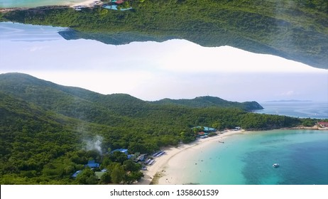 Aerial seascape with blue water, green hills on cloudy sky background, mirror horizon effect. Media. Beautiful sandy beach and high mountains covered with green trees, inception theme.