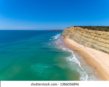 Aerial seascape, of Praia Porto de Mos (Beach and seaside cliff formations along coastline of Lagos city), famous destination in Algarve. South Portugal.