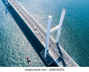 Aerial shooting of a bridge over the ocean. Top view.