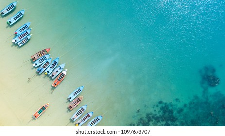 Aerial: Shoreline with thai fishing boats and long tail taxi boats parking along the sand beach of Thailand