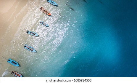 Aerial: Shoreline with thai long tail fishing and taxi boats parking along the sand beach of Thailand