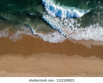 An aerial shot at 330 feet/100 meters looking down at the Pacific Ocean breaking along the Southern California Coast. Strong waves and currents leave the water sandy and foggy.