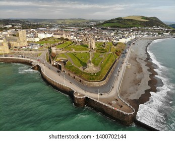 Aerial shot of Aberystwyth castle in warm sunset light with dramatic clouds in background.