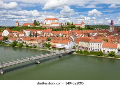 Aerial shot from above at Ptuj old city. Panoramic view of Ptuj castle on hill, Drava river, pedestrian and cycling bridge.