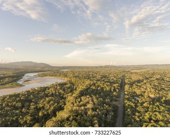 Aerial shot of an Amazonian highway at dusk in Ecuador with Rio Napo and Galeras mountain in the background.  Roads bring colonization and destruction of the rainforest to the Amazon Basin.
