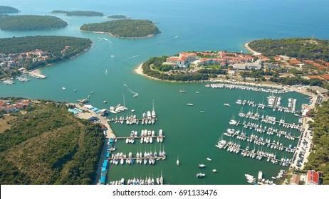 Aerial shot of anchored boats, motorboats and sailboats at marina piers in Pula, Croatia