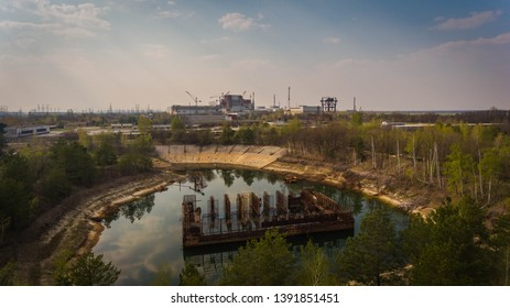 Aerial shot of an artificial lake with old metallic rods in Chernobyl zone in spring