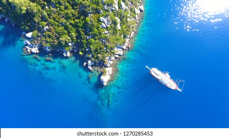 Aerial shot of beautiful blue lagoon and nature at hot summer day with sailing boat at open sea. Top view of gulet wooden yacht in Marmaris Mugla Turkey at Aegean Sea Turkey