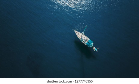 Aerial shot of beautiful blue lagoon at hot summer day with sailing boat. Top view.