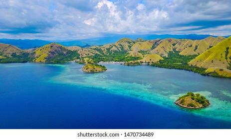 Aerial shot of beautiful blue lagoon at hot summer day with sailing boat. Komodo Island (Komodo National Park), Labuan Bajo, Flores, Indonesia