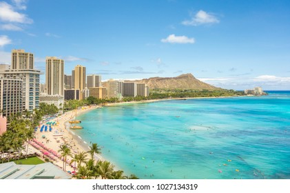 An aerial shot of the beautiful emerald green waters of Waikiki, Hawaii, with Diamond Head visible in the background, on a warm and clear sunny day.