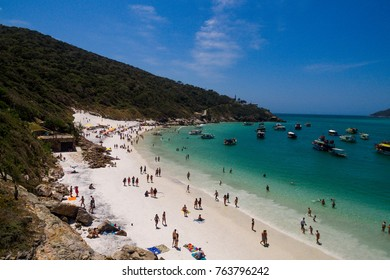 aerial shot of the beautiful and famous prainha beach in pontal do atalaia, arraial do cabo, rio de janeiro, brazil. wide shot showing the crowded beach and several boats