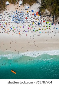 aerial shot of the beautiful and famous prainhas beach in pontal do atalaia, arraial do cabo, rio de janeiro, brazil. plain view showing the crowded beach and a banana boat with blue water