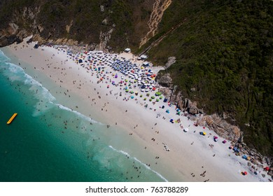 aerial shot of the beautiful and famous prainhas beach in pontal do atalaia, arraial do cabo, rio de janeiro, brazil. showing the whole crowded beach and the boats parked