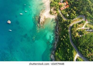 Aerial shot of beauty bay nature landscape with island, yachts and clear sea with turquoise water on Phuket. Serpentine road. Thailand. Drone photo. Top view.