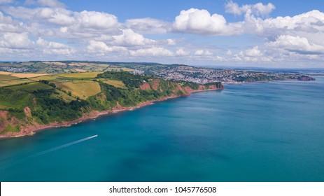 Aerial shot of boat passing South Devon coastline