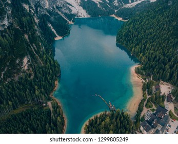 Aerial Shot of Braies Lake in Dolomites mountains forest trail in background, Sudtirol, Italy. Also known as Lago di Braies. The lake is surrounded by forest which are famous for scenic hiking trails