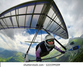Aerial shot of brave extreme hang glider pilot soaring the thermal updrafts above mountains taken with action camera