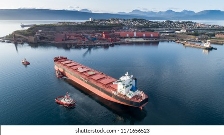 Aerial shot of a cargo ship approaching port terminal with help of towing ship, Narvik, Norway