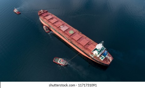 Aerial shot of a cargo ship approaching port with help of towing ship