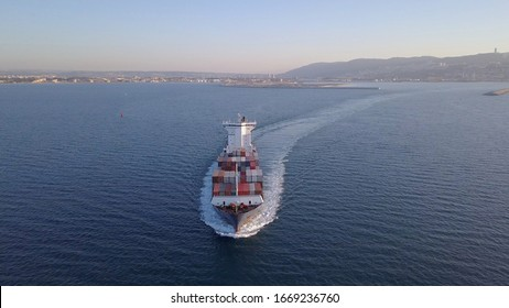 Aerial shot of container ship in ocean. Loaded vessel moves at calm water.