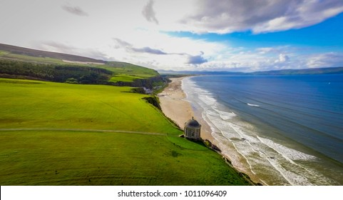 Aerial Shot of Downhill Strand with the Mussenden Temple over looking over the blue skies to the North and much darker weather to the South