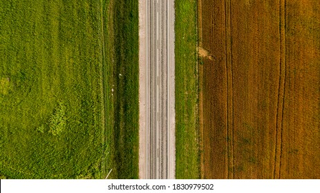 An aerial shot of an empty highway on a green and brownfield