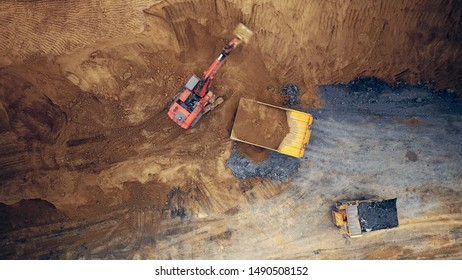 Aerial shot of a excavator digging into a large mining truck. Open pit coal mining