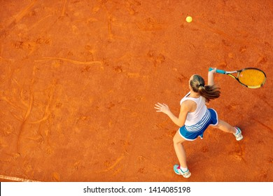 Aerial shot of a female tennis player on a court during match. Young woman playing tennis.High angle view.