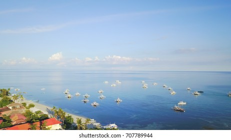 Aerial shot of Filipino boats floating on top of clear blue waters near the shore of Malapascua Island, Cebu, Philippines