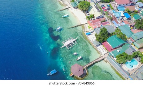 Aerial shot of Filipino boats floating on top of clear blue waters with schooling of sardines during sunny day near the shore of Moalboal, Cebu, Philippines