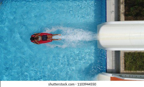 Aerial shot of girl on air mattress slide running into pool water