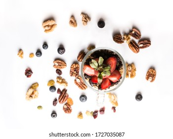 Aerial shot of a glass with yogurt, granola and fruits on a flat white background and seeds around.