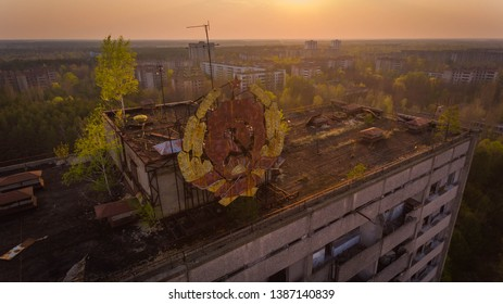 Aerial shot of a high ghost building in Chernobyl with a Soviet sign at sunset