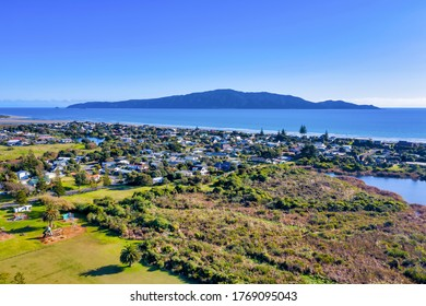an aerial shot of kapiti island taken from the quiet suburb of waikanae beach on the kapiti coast of new zealand. The small lake and wildlife sanctuary is seen in the foreground