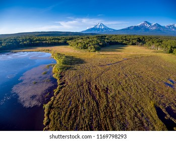 Aerial shot of lake and volcanoes at golden hour