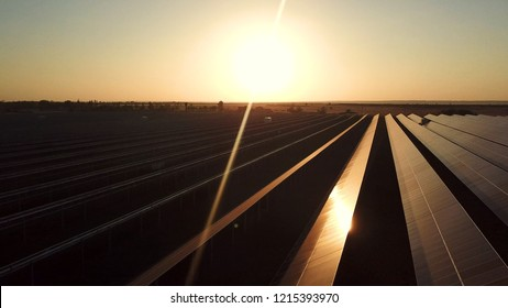 Aerial shot of a large industrial solar energy farm producing concentrated energy at sunset